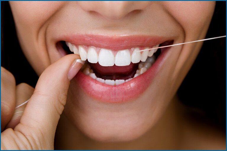 women flossing teeth