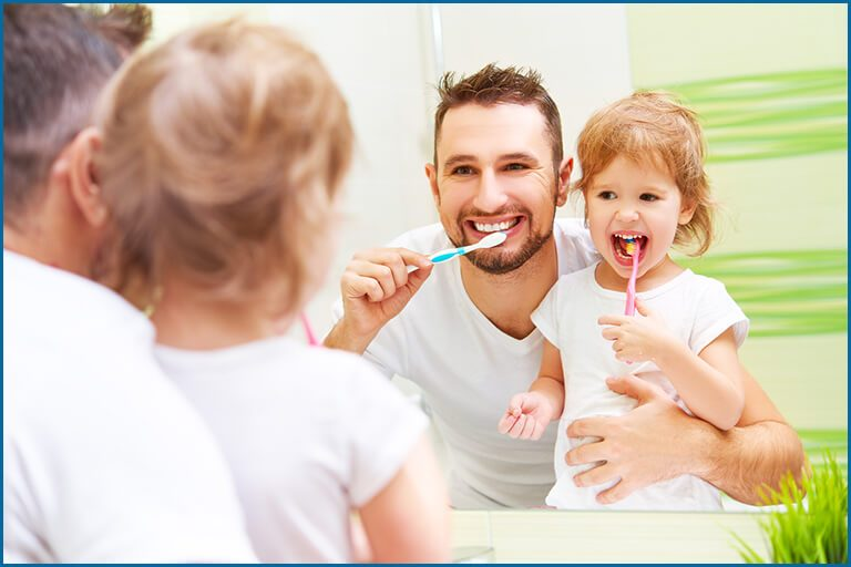 kid brushing with her father