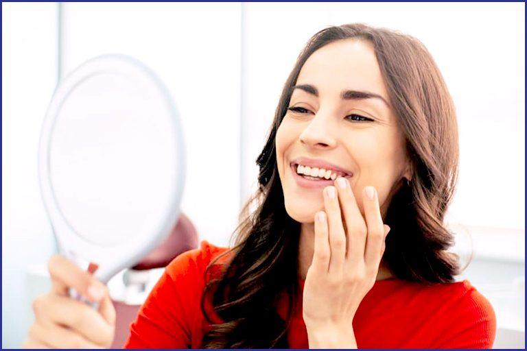 women looking at mirror and enjoying her smile